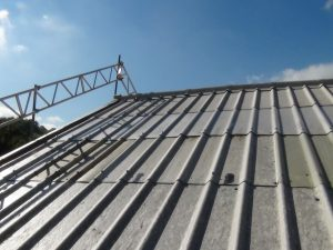 pitched asbestos roof that has been repaired